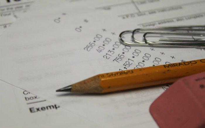 Imagem de números e lápis representando post sobre o que é IOF