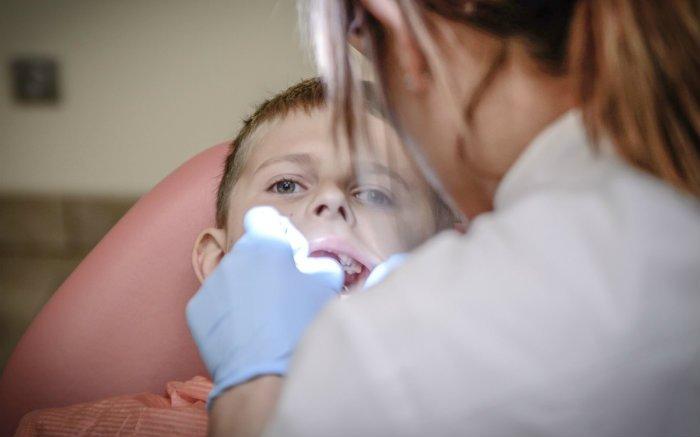 Imagem de criança no dentista para ilustrar texto sobre aparelho móvel